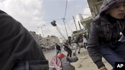 Palestinians throw stones at Israeli troops, Kalandia checkpoint between Jerusalem, Ramallah, March 30, 2012.