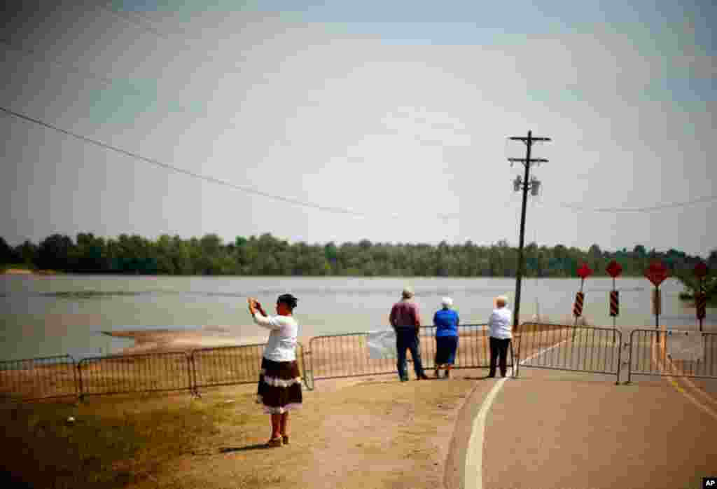 Residents look out at the Atchafalaya River as floodwaters approach Melville, Louisiana May 15. Army engineers on Saturday opened a key spillway to allow the Mississippi River to flood thousands of homes and crops, but spare New Orleans and Baton Rouge. (