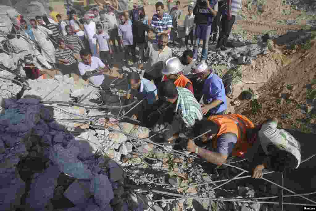 Palestinians search for victims under the rubble of a house that witnesses said was destroyed by an Israeli air strike east of Khan Younis in the southern Gaza Strip, July 24, 2014.