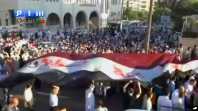 "Image from amateur video made available by Shamsnn on August 30, 2011 shows protesters carrying a large Syrian flag with the words ""Freedom, Syria"" written on it in Arabic  in Idlib. (The contents of this image cannot be independently verified)"