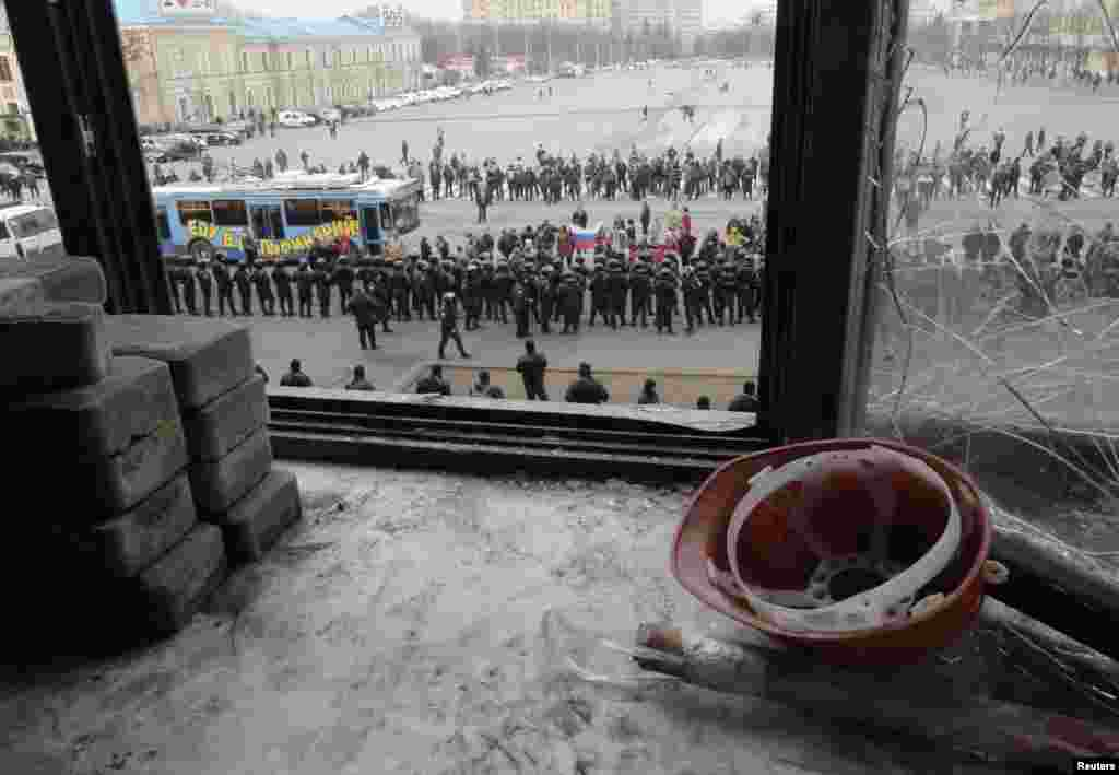 A view through a broken window of the regional administration building shows a cordon of Interior Ministry members blocking a group of pro-Russian protesters in Kharkiv, Ukraine, April 8, 2014.
