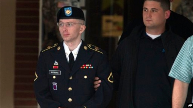 Army Pfc. Bradley Manning is escorted out of a courthouse after the start of the sixth week of his court martial, in Fort Meade, Maryland, July 8, 2013.