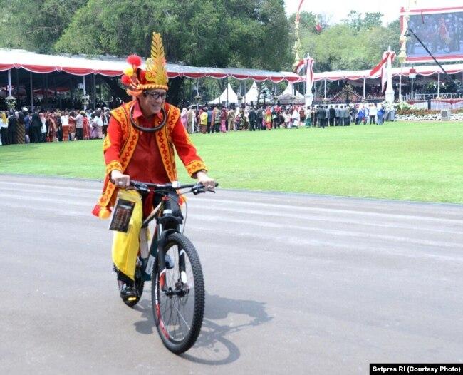 Menhukham, Yasonna Laoly, yang mengenakan pakaian tradisional Nias nampak mencoba mengendarai sepeda hadiah dari Presiden Joko Widodo (Courtesy: Setpres RI)