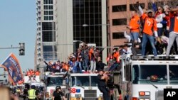 Members of the Denver Broncos wave to adoring fans from atop a fleet of firetrucks during a Super Bowl victory parade in Denver, Feb. 9, 2016.