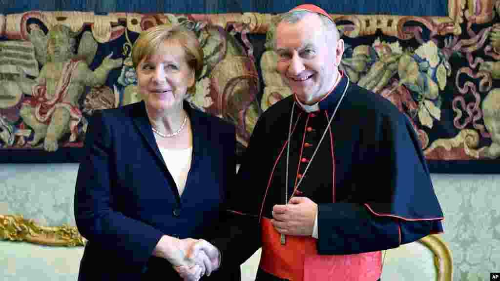 La chancelière allemande Angela Merkel serre la main avec le secrétaire d'État du Vatican, Pietro Parolin, après son auditoire privé avec le pape Francis, au Vatican, le 17 juin 2017.