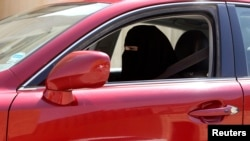 FILE - Defying social norms in place at the time, a woman drives a car, in Saudi Arabia, Oct. 22, 2013.