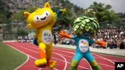 Maskot untuk Olimpiade Rio 2016 (kiri) dan Olimpiade Paralimpik dalam peluncuran perdana di sekolah negeri Santa Teresa di Rio de Janeiro, Brazil (24/11). (AP/Felipe Dana)