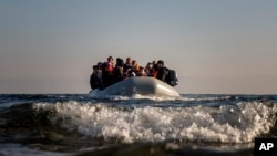 FILE - Refugees and migrants approach the Greek island of Lesbos on a dinghy after crossing the Aegean sea from the Turkish coast, on Monday, Dec. 7, 2015.