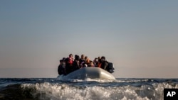 Refugees and migrants approach the Greek island of Lesbos on a dinghy after crossing the Aegean sea from the Turkish coast, on Monday, Dec. 7, 2015.