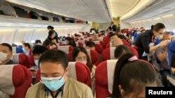 တ႐ုတ္ႏုိင္ငံ Shenzhen Baoan ေလဆိပ္မွထြက္ခြာမည့္ China Eastern ေလေၾကာင္းလုိင္း ေလယာဥ္ေပၚမွ ခရီးသည္မ်ား။ (ေမ ၁၉၊ ၂၀၂၀)