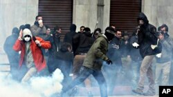 Protesters try to avoid a tear gas canister during clashes in central Athens, February 23, 2011