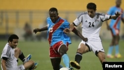 Kaluyituka Dioko de la RDC prend le contrôle de la balle face à Ahmed Khayili de l'Egypte, à droite, lors du match amical RDC-Egypte à Doha, Qatar, 2 mars 2012.