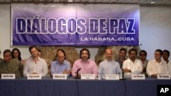 FILE Revolutionary Armed Forces of Colombia (FARC) peace negotiators and Members of Colombia's government negotiating team give a joint statement in Havana, Cuba, June. 4, 2015.