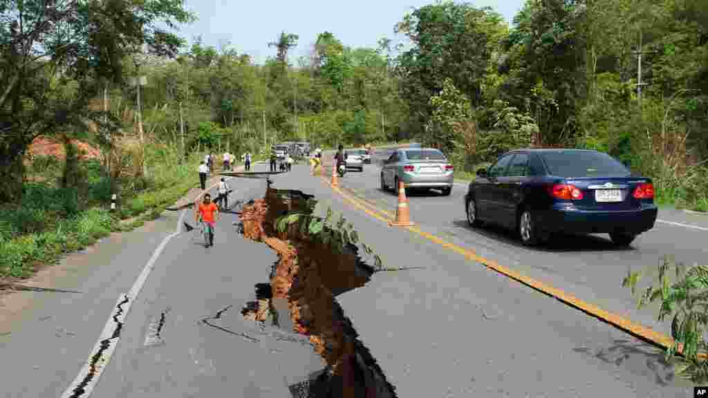 Motorists navigate their way around a cracked section of highway as people examine the damage after an earthquake, Chiang Rai, northern Thailand, May 6, 2014.