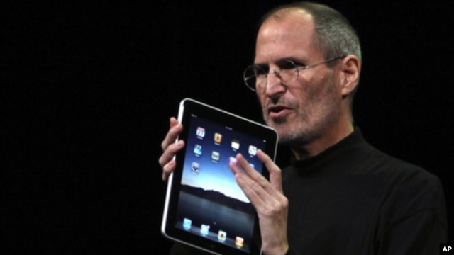 Apple Chief Executive Officer Steve Jobs holds the new 'iPad' during the launch of Apple's new tablet computing device in San Francisco, California