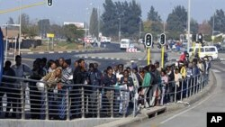 South African commuters line up at a bus stop in Soweto on 17 May 2010 during a strike by rail workers