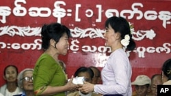 Burma's pro-democracy leader Aung San Suu Kyi (R) presents an Unknown Hero Award to a relative of Than Naing Oo, who is currently in prison, at National league for Democracy (NLD) head office in Yangon, April 17, 2011