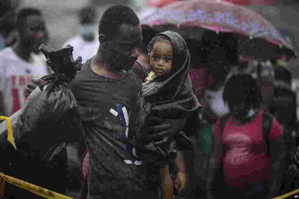 A Haitian migrant carries a baby to a boat that will take them to Capurgana, on the border with Panama, from Necocli, Colombia.