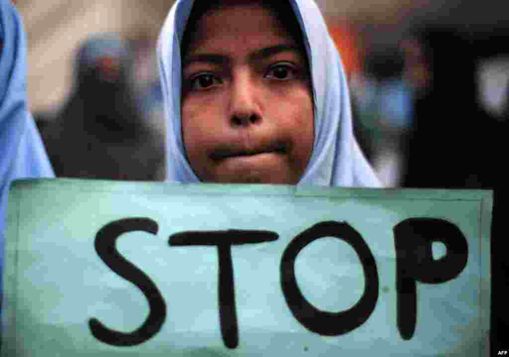 A Shi'ite student of Imamia Students Organization (ISO) holds a poster during a protest against an attack by Taliban militants at an army-run school in Peshawar the previous day, in Karachi.