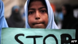FILE - A Shi'ite student of Imamia Students Organization (ISO) holds a placard during a protest against an attack by Taliban militants at an army-run school in Peshawar.