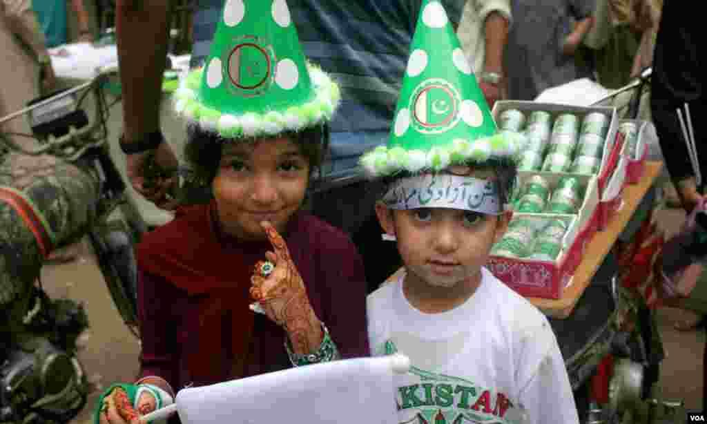 یوم آزادی کی مناسبت سے دو بچے قومی پرچم کے رنگوں سے سجی ٹوپیاں پہنے ہوئے
