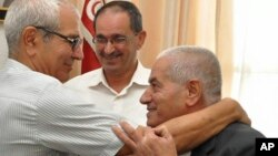 Houcine Abassi, secretary general of the Tunisian General Labour Union (UGTT), right, is congratulated by unidentified union members in his office at the headquarters in Tunis, Tunisia, Friday, Oct. 9, 2015. Abassi is one of the four members of the Tunisian National Dialogue Quartet to be awarded the 2015 Nobel Peace Prize on Friday by the Norwegian Nobel Committee. (AP Photo)