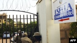 Ugandan police officers stand by the entrance of the Esella Country Hotel after police raided a gay rights workshop which was taking place in the hotel in Kampala, June 18, 2012.