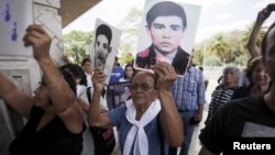 Relatives of war victims protest against Carlos Vides, a former Salvadoran minister of defense, upon his arrival at San Salvador's Oscar Romero airport, April 8, 2015.