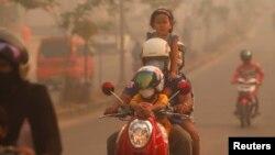 Một gia đình đi xe máy qua lớp khói mù trong thị trấn Duri ở tỉnh Riau của Indonesia, ngày 24/6/2013.