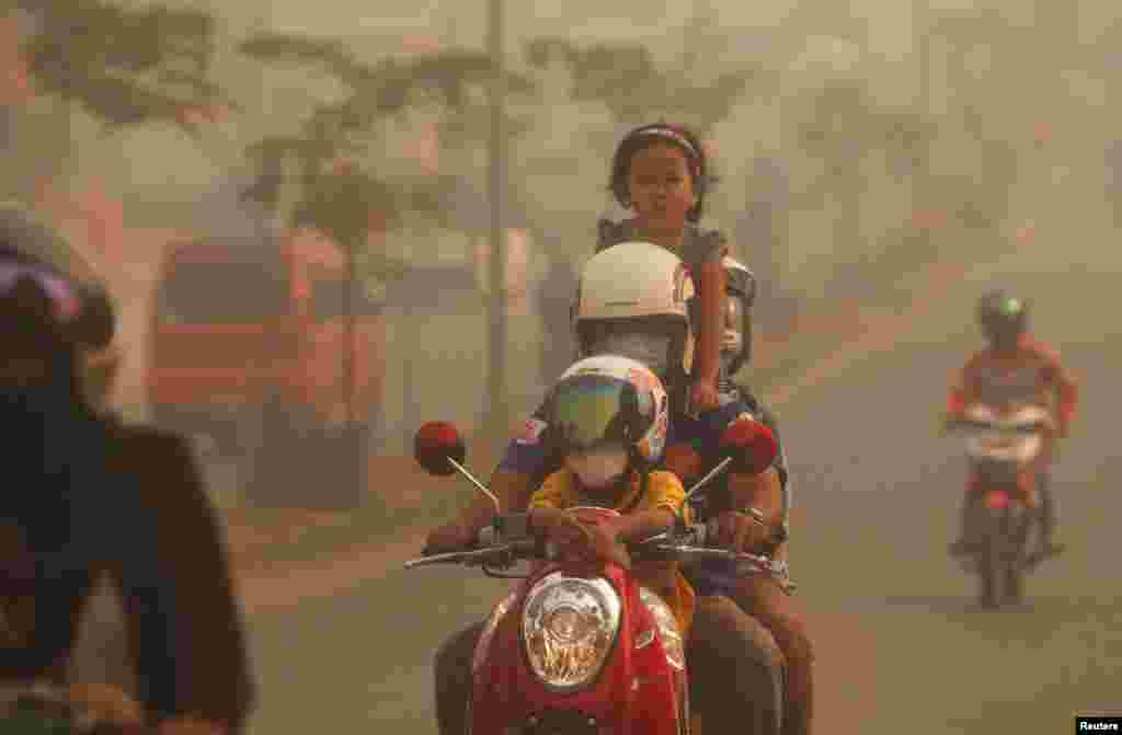 A family rides on a motorcycle in the haze which hit Duri on Indonesia's Riau province. Indonesian police arrested two farmers for illegally starting fires to clear land in Sumatra - the first detentions linked to blazes that have blanketed neighboring Singapore and Malaysia with thick smog for days.