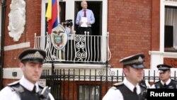Ông Assange đứng trên bao lơn đại sứ quán Ecuador ở London. Ông Assange được Ecuador cho phép tỵ nạn, nhưng chính phủ Anh không cho ông rời London vì Anh có nghĩa vụ giải giao ông cho Thụy Điển, nơi đã có trát bắt ông