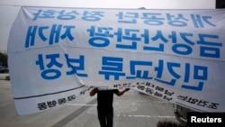 Một người tham gia biểu tình đòi tái khởi động các cuộc đối thoại giữa hai miền Triều Tiên. Tấm băng rôn ghi dòng chữ: 'Bình thường hóa khu Kaesong, tái thiết lập các chương trình tour du lịch của ông Geumgang, bảo đảm sự tương tác phi chính phủ.' REUTERS/Kim Hong-Ji