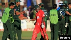 FILE: Zimbabwe's batsman Prosper Utseya (C) leaves the field as Pakistan's players celebrate their win after beating Zimbabwe during their second and last Twenty20 cricket match in Harare September 18, 2011. REUTERS/Philimon Bulawayo (ZIMBABWE - Tags: SPORT CRI