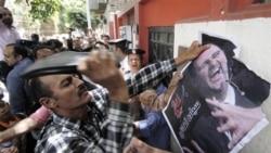 یک معترض سوری، طی تظاهراتی که مقابل سفارت سوریه در قاهره پایتخت مصر برگزار شد، با کفش به تصویر بشار اسد می زند - ۲۶ آوریل ۲۰۱۱