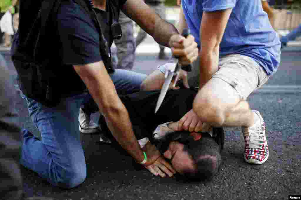 People disarm an Orthodox Jewish assailant shortly after he stabbed participants at the annual Gay Pride parade in Jerusalem. Six participants were wounded during the march, police said.
