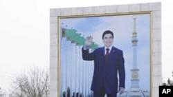 A woman walks past a board displaying a portrait of Turkmenistan's President Kurbanguly Berdymukhamedov in Ashqabat, February 10, 2012.