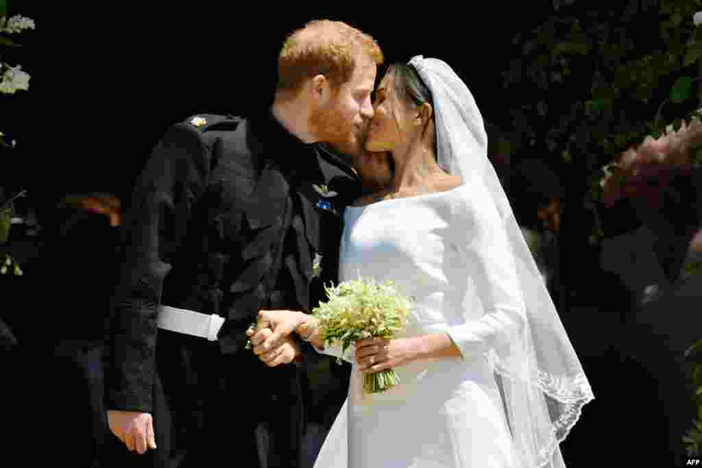 Britain's Prince Harry, Duke of Sussex kisses his wife Meghan, Duchess of Sussex as they leave from the West Door of St George's Chapel, Windsor Castle, in Windsor