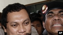 Tax official Gayus Tambunan is escorted by police officers as he arrives at a district court for his corruption trial in Jakarta, Indonesia, Wednesday, Jan. 19, 2011