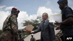 FILE - Victor Tokmakov, first secretary of the Russian Embassy, presents graduation diplomas to graduating recruits in Berengo, Aug. 4, 2018. Russian military consultants set up training for the Central African Armed Forces after delivering weapons to the country.