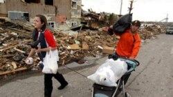 در این تصویر دو تن از دانشجویان دانشگاه میسوری را در حال حمل آنچه پس از گردباد برایشان باقی مانده، مشاهده می کنید. ۲۴ مه ۲۰۱۱