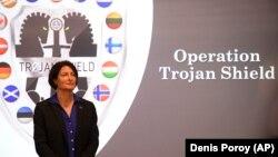 """Agen FBI Suzanne Turner berdiri di depan logo Operasi """"Trojan Shield"""" di San Diego, CA, AS Selasa (8/6)."""