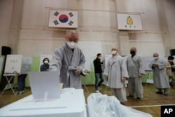 A Buddhist monk wearing a face mask to help protect against the spread of the new coronavirus casts his early vote for the upcoming parliamentary election at a polling station in Seoul, South Korea, Friday, April 10, 2020.