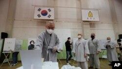 Seorang bhiksu mengenakan masker untuk melindungi dari penyebaran virus corona saat memberikan suaranya dalam pemilihan parlemen di i sebuah TPS di Seoul, Korea Selatan, Jumat, 10 April, 2020.