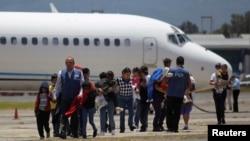 Des familles guatémaltèques déportées de Phœnix, à Arizona, marchent sur le tarmac après l'atterrissage de leur avion à l'aéroport de la ville de Guatemala, 22 juillet 2014.