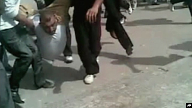 A still image taken from an amateur video purportedly taken on April 22, 2011 shows a protester being carried by a group of other protesters during a demonstration in the city of Homs, Syria