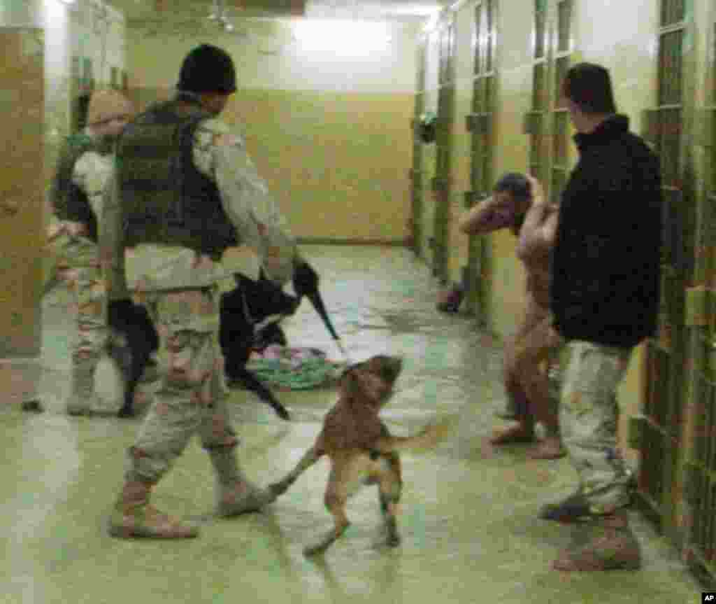 This image obtained by The Associated Press shows Sgt. Michael Smith, left, Sgt. Santos Cardona, second right, detainee Mohammed Bollendia and Pvt. Ivan L. Frederick II, right, during an incident at the Abu Ghraib prison in Baghdad, Iraq on December 12, 2003.