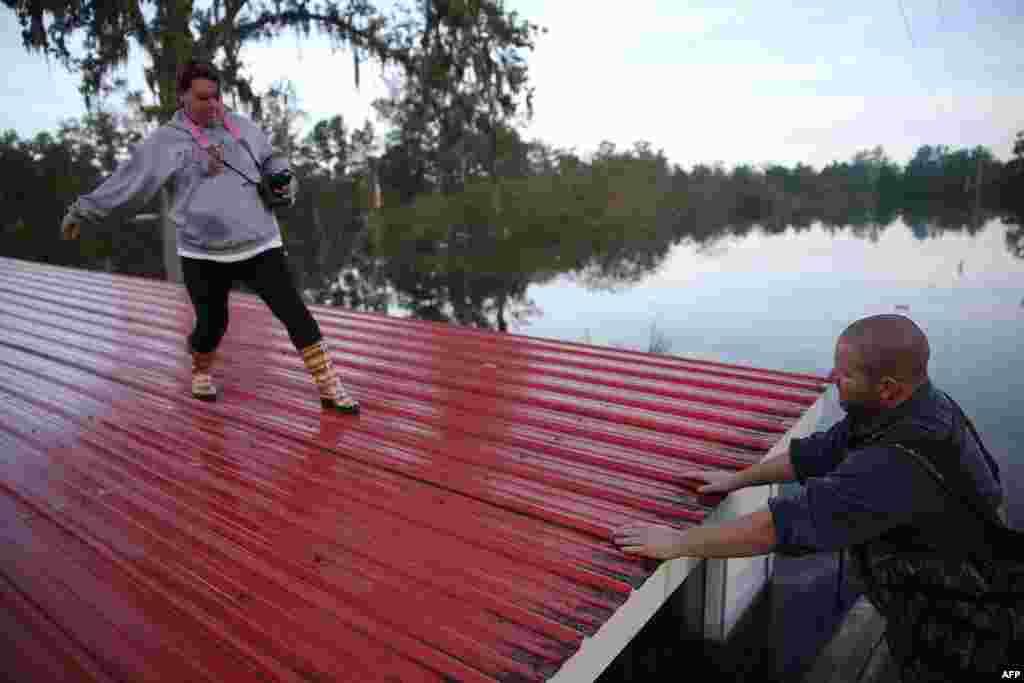 Wendy Lawshe (trái) bước đi trên mái nhà của cha cô trong khi chồng cô đợi trong thuyền khi họ đem đi những bức hình treo trên tường của ngôi nhà bị ngập lụt ở thành phố Andrews, bang South Carolina, Mỹ.