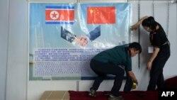 지난해 9월 북한 평양에서 열린 '가을철 국제 상품 전람회'에 참가한 중국 업체 관계자가 홍보물을 부착하고 있다. (자료사진)