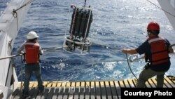 MBARI Scientists aboard Research Vessel Western Flyer shown recovering a water sampling device in the North Pacific Ocean, which is used to collect algae. (photo credit: Adam Monier)