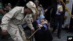 Un rebelle libyen aidant une femme évacuée de Misrata à bord du ferry alabanais Red Star 1 et débarquant au port de Benghazi